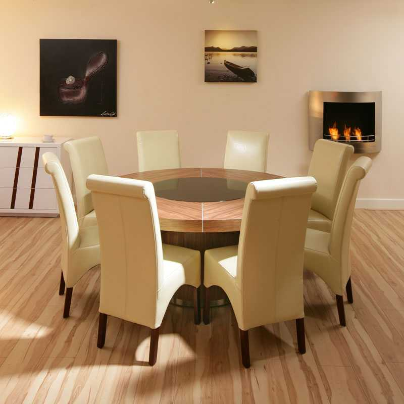large round walnut dining table with 8 high back ivory leather chairs